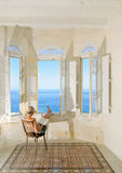Young pregnant woman by the window facing the sea. Young pregnant woman reading a book by the window facing the sea. Malta Royalty Free Stock Photo