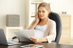 Young pregnant woman working in office. Young pregnant woman working in home office Royalty Free Stock Photo