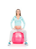 A young pregnant woman working out with a fitness ball Stock Photography