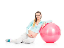 A young pregnant woman working out with a fitness ball Royalty Free Stock Photos