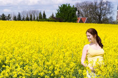 Young pregnant woman in yellow flower field Royalty Free Stock Photo