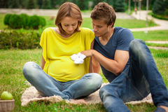 Young pregnant woman with young man on picnic Royalty Free Stock Image