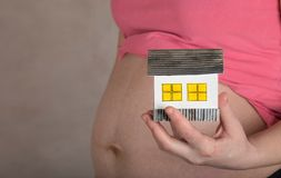 Young pregnant woman keeps small handmade house. Young pregnant between 30 and 35 years old woman keeps small handmade house. Closeup royalty free stock images