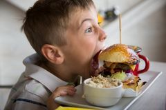 Young prepares to bite a big hamburger. Little child starts to eat his meal royalty free stock image