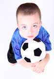 Young preschool boy laying on a soccer ball. On white background Royalty Free Stock Images