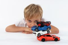 Young preschool child seeming bored playing with the toys. He looks unhappy or disappointed stock photo