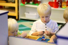 Young Preschool Children Playing Building Blocks in School Class. Some young preschool children are at their school classroom playing with building block toys Royalty Free Stock Images