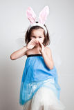 Young Asian girl in bunny rabbit ears. Young preschool girl wearing party dress and bunny rabbit ears, studio background royalty free stock photos