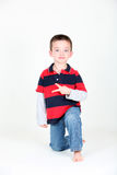 Young preschooler kneeling on white background. Making a peace sign Royalty Free Stock Photos