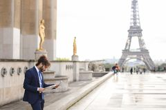 Hispanic journalist close to Eiffel Tower reading newspaper and. Young pressman reading newspaper article near Eiffel Tower and looking at watch. Handsome boy Stock Image