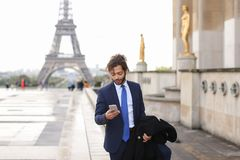 Hispanic journalist close to Eiffel Tower reading newspaper and. Young pressman reading newspaper article near Eiffel Tower and looking at watch. Handsome boy Royalty Free Stock Image