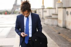 Hispanic journalist close to Eiffel Tower reading newspaper and. Young pressman reading newspaper article near Eiffel Tower and looking at watch. Handsome boy Royalty Free Stock Photo