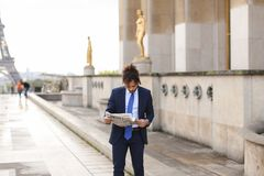 Hispanic journalist close to Eiffel Tower reading newspaper and. Young pressman reading newspaper article near Eiffel Tower and looking at watch. Handsome boy Stock Images
