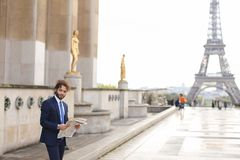 Hispanic journalist close to Eiffel Tower reading newspaper and. Young pressman reading newspaper article near Eiffel Tower and looking at watch. Handsome boy Stock Photos