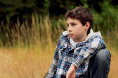 A Young Preteen Boy in Field. A young preteen country boy sitting in a field of tall grass. Shallow depth of field. Copy Space Royalty Free Stock Image