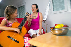 Young preteen girl having guitar lesson at home Royalty Free Stock Images
