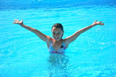 Young preteen girl in pool with arms in a V shape Stock Photos