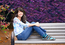 Young preteen girl sitting on park bench outdoors Stock Image