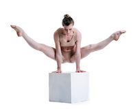 Young pretty acrobat posing with cube in studio Stock Image