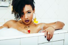 Young pretty african american girl taking bath with foam, lifestyle people concept royalty free stock photography