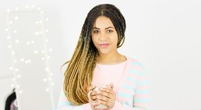 Young pretty African American millennial woman with natural dreadlocks hair smiling. Grey Background stock photos