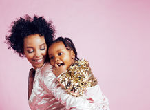 Young pretty african-american mother with little cute daughter hugging, happy smiling on pink background, lifestyle Stock Photos