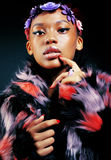 Young pretty african american woman in spotted fur coat and flow Royalty Free Stock Photos