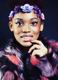 Young pretty african american woman in spotted fur coat and flowers jewelry on head smiling sweet etnic girl Stock Photography