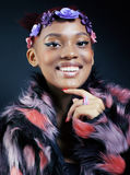 Young pretty african american woman in spotted fur coat and flowers jewelry on head smiling sweet etnic make up bright Royalty Free Stock Image