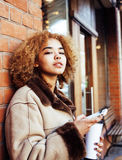 Young pretty african american women drinking coffee outside in cafe, modern business woman lifestyle concept Stock Images