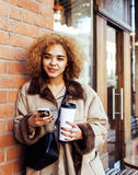 Young pretty african american women drinking coffee outside in cafe, modern business woman lifestyle concept Stock Photos
