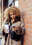 Young pretty african american women drinking coffee outside in cafe, modern business woman lifestyle concept Stock Image