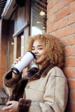 Young pretty african american women drinking coffee outside in cafe, modern business woman lifestyle concept Royalty Free Stock Photos