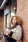 Young pretty african american women drinking coffee outside in cafe, modern business woman lifestyle concept Stock Photo