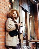 Young pretty african american women drinking coffee outside in cafe, modern real business woman lifestyle concept Royalty Free Stock Images