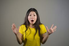 Young pretty and amazed Asian Korean girl astonished and shocked in wonder and surprise gesturing with hands and wide open mouth i stock images