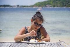 Young pretty anf happy Asian Chinese woman having lunch at resort beach restaurant in front of the sea eating healthy food. Enjoying summer holiday trip Stock Image