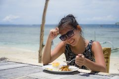 Young pretty anf happy Asian Chinese woman having lunch at resort beach restaurant in front of the sea eating healthy food. Enjoying summer holiday trip Royalty Free Stock Image