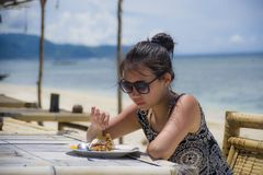 Young pretty anf happy Asian Chinese woman having lunch at resort beach restaurant in front of the sea eating healthy food. Enjoying summer holiday trip Royalty Free Stock Photos