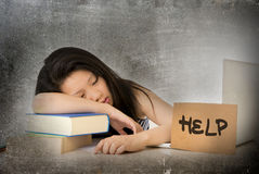 Young pretty Asian Chinese woman student asleep on her laptop studying overworked with help sign on her desk Stock Photos