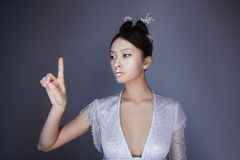 Young pretty asian futuristic woman pressing an imaginary button, empty space for buttons Royalty Free Stock Image