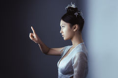 Young pretty asian futuristic woman pressing an imaginary button, empty space for buttons Stock Photo