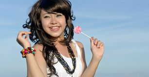 Young pretty asian girl enjoys eating candy Royalty Free Stock Image