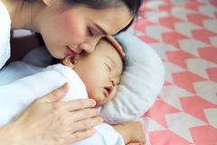 Young pretty Asian mother hugging her sleeping cute baby on the bed. The mother closing her eyes when touching her child softly royalty free stock photography