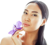 Young pretty asian woman with flower orchid close up isolated spa Stock Photo