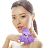 Young pretty asian woman with flower purple orchid close up isolated on white background spa, healthcare concept Royalty Free Stock Images