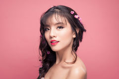 Young pretty asian woman with flowers on hair close up on pink b stock photos