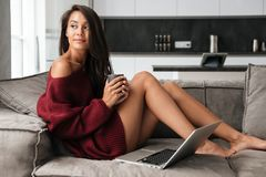 Young pretty asian woman in sweater holding cup of coffee Royalty Free Stock Photography