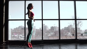 Young pretty athletics girls skipping on drill at gym against barred window. 20s 4k.  stock video