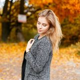 Young pretty attractive stylish woman in a gray elegant coat resting outdoors in a park. Fashionable girl fashion model enjoys royalty free stock photography